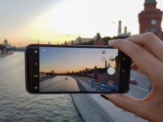 Female hand takes a photo on your smartphone city sunset