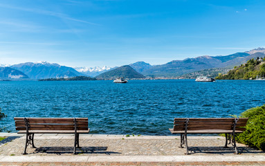 Landscape of Lake Maggiore with two benches on the shore in the foreground, Italy