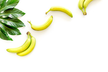 Exotic fruits. Fresh ripe bananas near big tropical leaf on white background top view copyspace