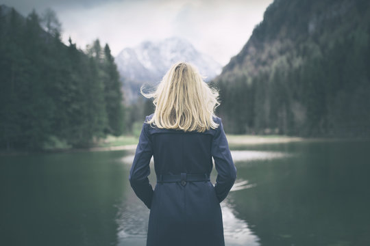 Blonde woman standing backwards and watching magic lake in mountainous country landscape.
