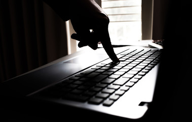 Fototapeta Silhouette black and white hands of anonymous hackers typing code on keyboard of laptop for remotely reach and receiving personal information online networking, Internet Crime Payment Security Concept