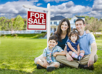 Young Family With Children In Front of Custom Home and For Sale Real Estate Sign.