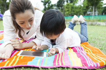 Mom and son are touching the tablet in the park