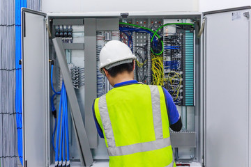 Electrician with a screwdriver macro connect wires on the background of electrical cabinet with relays and terminal blocks.