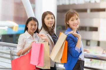 happy three women friends and shopping bags in they hand