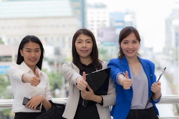 Three business Asian woman showing thumbs up