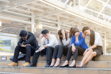 Group of business man and woman sitting on staircase stressed of they work