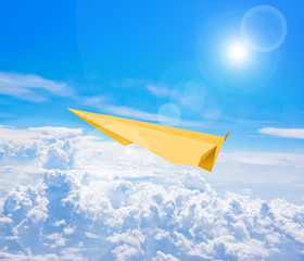 Yellow paper plane flying against blue sky