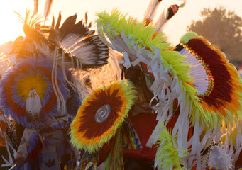 Pow Wow Headdresses worn by Native American men dancing at a pow wow. The red, orange, yellow, blue and white feathers are back lit by the setting sun.