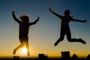 two women or girls silhouette active jumping she funny and happy