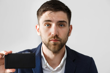 Business Concept - Handsome Business man take a selfie of himself with smartphone. White Background.