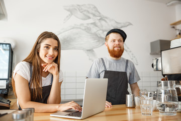 Coffee Business Concept - Cheerful baristas looking at their laptop for online orders in modern coffee shop.
