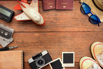 Top view of travel accessories with a passport, camera, notebook, glasses on wooden                                                   background