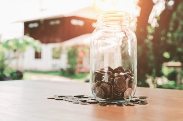 saving money in jar glass and house background, concept finance by home