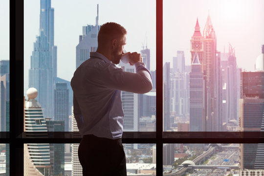 Businessman Drinking Coffee And Looking At City Skyline