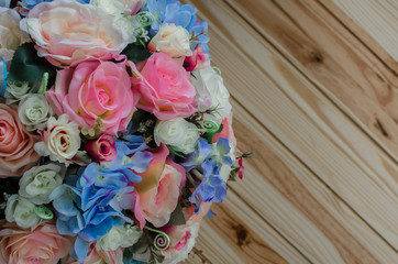 Roses bouquet over wooden table. Top view with copy space