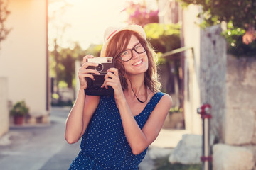 Cute young female holding a retro-styled camera outdoors.