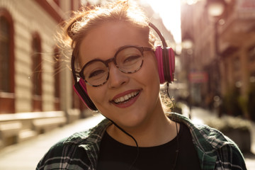 Beautiful woman listening to music on the street with headphones.