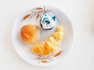 Pastries and cup cakes on white plate