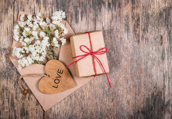 Flowers in an envelope, wooden heart and box with gift. Copy space