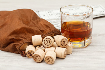 Board game lotto on white desk. Wooden lotto barrels with bag, game cards and glass of whiskey