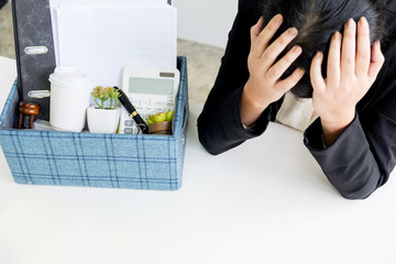 sadness pretty female office worker is fired packing personal belongings sitting on working desk feeling upset and thinking future job.