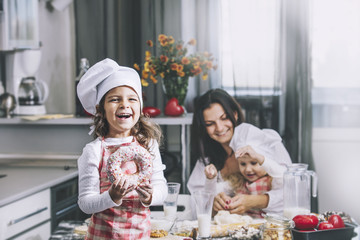 Small girl child eats a donut with my mom and sister happy cook at the table in the kitchen is lovely and beautiful