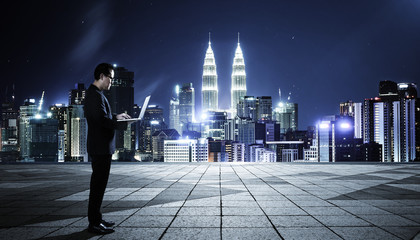 Businessman using laptop with cityscape background , night scene .