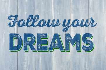 Blue wooden wall with the inscription Follow your dreams