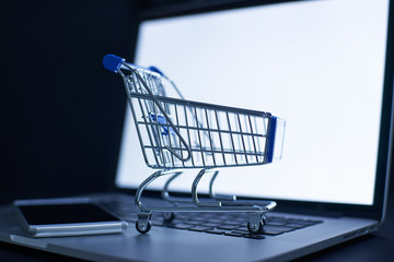 Shopping cart or trolley in front of Laptop , online marketing and business trading concept.
