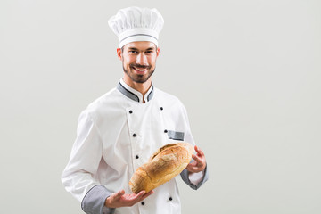 Baker holding bread on gray background.