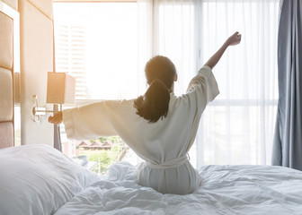 Easy lifestyle young Asian girl waking up in the morning taking a rest relaxing in hotel room for world lazy day concept