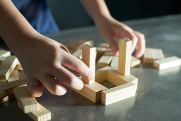 Hand of kid playing a blocks wood tower game of architectural project .Selected focusing .