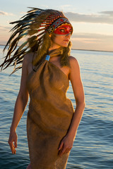 Woman dressed in an american indian style stands on the seashore