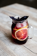 Black-currant lemonade with lemon slices, berries, ice cubes and purple basil in a glass jar. Selective focus.