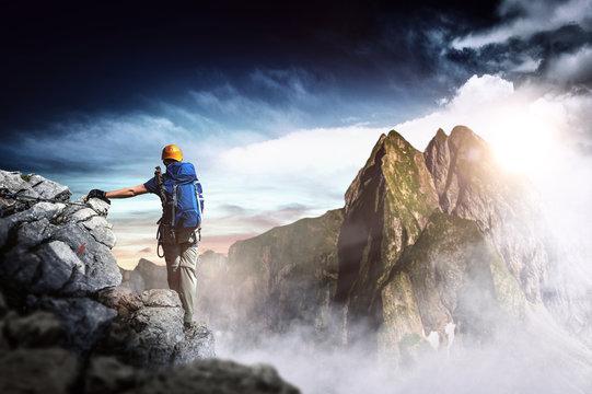 Bergsteiger erreicht den Gipfel eines Berges. Panorama.