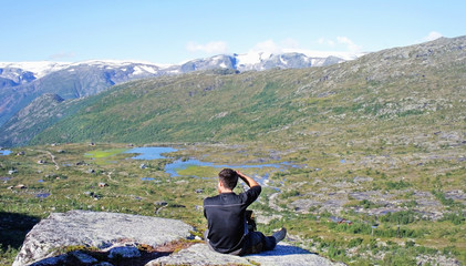 The man is seating on the rock and taking picture, top view of valley between mountains, hiking way to Trolltunga cliff (The Troll's tongue), Odda, Norway
