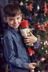 A boy at a New Year tree with a nutcracker