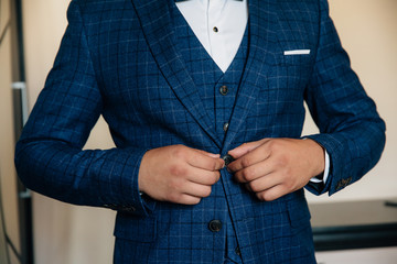 Close-up businessman groom wearing his jacket. Concept of men stylish elegance clothes