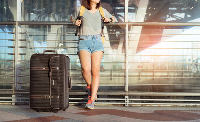 Young girl asian traveler standing with carrying hold suitcase luggage and passenger for tour travel booking ticket flight in airport international vacation time in holiday rest and relaxation.