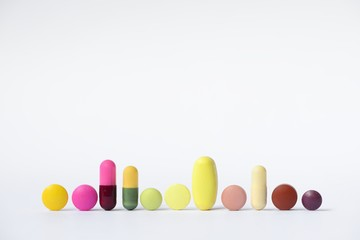 Colored tablets and capsules in a row, 11 pieces, white background