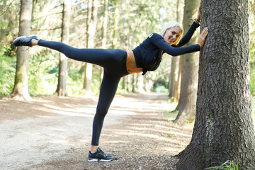 Picture of athlete on stretch near tree