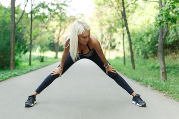 Picture of sports girl stretching in park