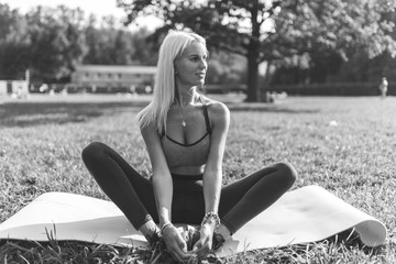 Black and white photo of sports girl sitting on rug