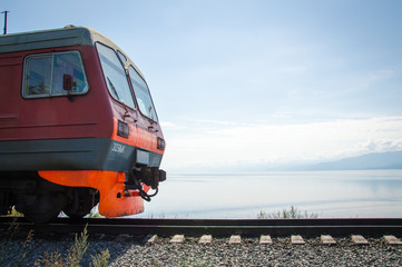 Train on rails in front of idyllic landscape of Lake Baikal, Siberia, Russia - on a day in summer 2017