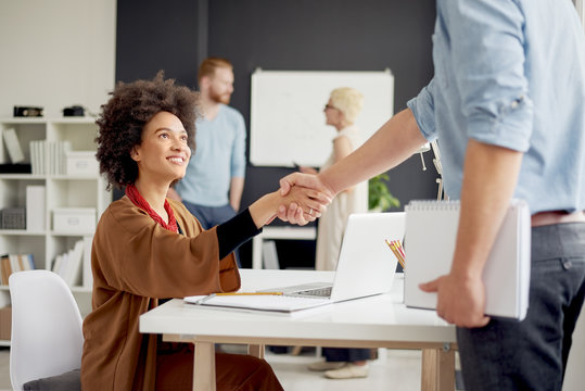 Colleagues shaking hands in modern office