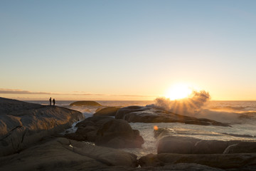 Couple watching the sunset over the ocean with crashing waves