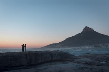 Couple watching the sunset over the ocean with Lion's Head