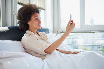 Young woman making video call over mobile phone while lying on the bed