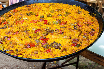 Large flat frying pan with cooked homemade Spanish paella with variety of meats, vegetables, rice, tomato sauce, spices. Outdoors, vibrant orane red and yellow colors.